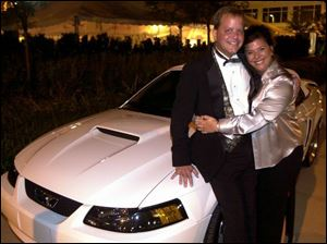 NEW TOY: Jeff and Tammy Fretti smile happily after they won the bidding for the 2003 Ford Mustang convertible.