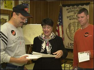 Sandy Isenberg dispenses literature to supporters Craig Mead, left, and Nick Dukeshire at a union hall.