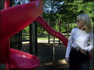 Barbara Lane, Toledo's superintendent of parks, looks over a slide at Ottawa Park.