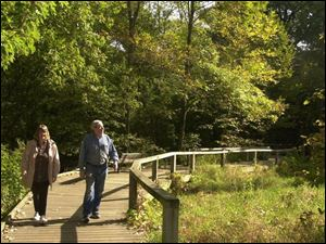 Jeanne and Bill Rouppas use the boardwalk at Wildwood Preserve Metropark. The park system has added 920 acres in the last decade, including an expansion of Wildwood, and more growth is eyed.