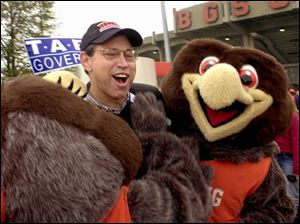 Gov. Bob Taft, decked out in Bowling Green State University paraphernalia, is greeted by BGSU mascots Frieda and Freddy as he arrives to attend a football game.