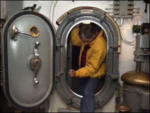 Toby Oothoudt demonstrates what a tight fit the hatches are on the World War II submarine USS Cod.
