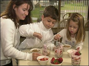 Betty Bassett and children, J.T., 7, and Victoria, 4, fix Yogurt Granola Parfaits.