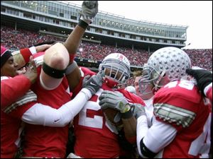 Ohio State free safety Will Allen (26) is mobbed by teammates after intercepting the last offensive play by Michigan.