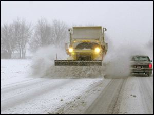 A plow pushes snow off the road and onto a passing car on State Rt. 51 east of Genoa.