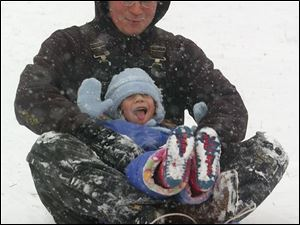 Four-year-old Kasey Hoffman enjoys a wild ride through the snowflakes with her father, Mike, on a hill at Waite High School in East Toledo. The National Weather Service said 4 inches of snow fell on the area yesterday, which was a lot of fun if you weren't trying to drive in it.