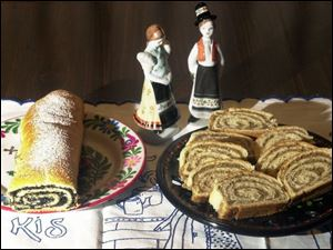 An unsliced poppyseed roll, left, and slices of a nut roll, made by Mary Lou Tomsic are served on Hungarian plates that the family treasures.