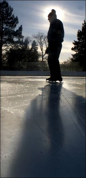 Lone skater Don Metzger casts a dark shadow as he takes his time strolling around the Ottawa Park skating rink during a sunny and mild winter afternoon. He skates at the park about 3 to 4 times a week, while his wife sits inside the rink and reads a book.
