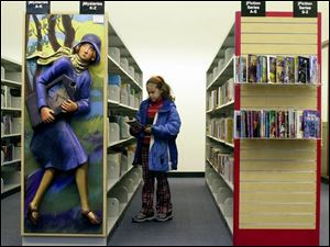 Ciera Wilkinson, 10, of Sylvania looks over the book selection at the Toledo-Lucas County Public Library downtown.
