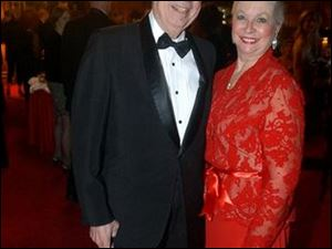 Richard S. Baker with his wife, Barbara, who brightened the party in her attractive red gown.