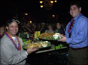 SEAFOOD SERVINGS: Andy Anderzak, left, and Brian Epstein, co-chairmen of the Barefoot at the Beach party, pass around some of the abundant seafood platters.