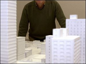 'We want to provide some harmony,' says Bob Seyfang, retired architect and developer, at Design Center headquarters on North Huron Street behind a tabletop model of downtown Toledo.
