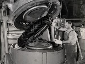 A worker removes a heavy-duty tire from a curing mold at a Firestone plant in Akron, once the world's rubber capital.