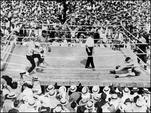 Jess Willard, right, crumples on the mat after a battering by boxer Jack Dempsey during a July 4, 1919, title fight at Bay View Park in Toledo.
