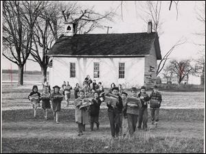 First and second grade pupils in 1950 carry school supplies from their old one-room school house in Riley Township across the field to a new school.