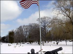 Military graves and artifacts honor veterans at historic Woodlawn Cemetery.