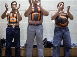 From left, Bettsville basketball parents Tim Weber, David Hawk and Bob Green spell out their support during a sectional game against New Riegel. But not even these drastic measures worked.