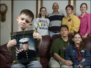 While Marine reservist Cpl. Lance Kokensparger, in portrait, is fighting Iraq, his son, in foreground, Max, 3; wife, Barb, and daughter, Hali, 8, along with his sister, Jennette, 13; father, Larry; mother, Kathy, and sister, Jessica, 16, offer support at home.