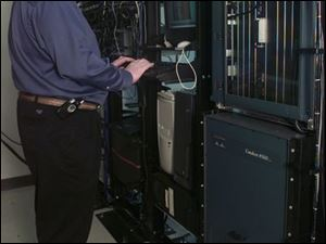 Dan Baker checks Internet servers at TotalLink facility.