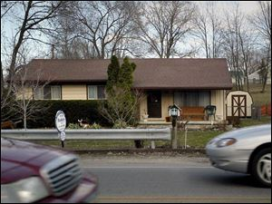Traffic zips past a house offered for sale on South Wheeling Street in the suburb of Oregon, east of To