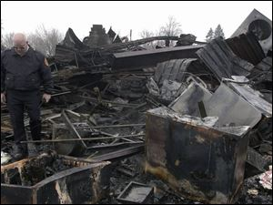 Joe Tuckey, Tecumseh fire chief, pokes through the ruins of Fabricare Dry Cleaners & Coin Laundry at 117 Herrick Park.