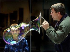 Mekkel Richards, 11, is all smiles as he watches Tom Sklar blow an oversized bubble at COSI-Toledo. The two were among a group of Brooklyn Elementary pupils, staff, and parents on a field trip to the science museum yesterday.