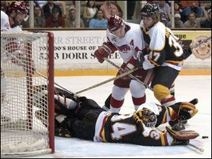 Cincinnati goalie Greg Hewitt makes a save as Steve Rodberg tries to get Toledo's Tim Verbeek out of the way.