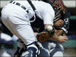 Carlos Lee of the Chicago White Sox scores by knocking the ball from the grasp of Detroit catcher Brandon Inge.