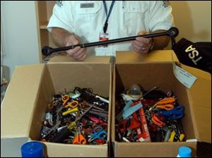 Mickey Thompson, a Toledo Express Airport screener, displays the banned items seized from airplane travelers.