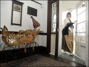 A Gendron baby carriage manufactured about 1870 in Toledo that's part of an Ohio Bicentennial exhibit is parked inside the entrance to the Wolcott House Museum as employee Peggy Earhart arrives for work.