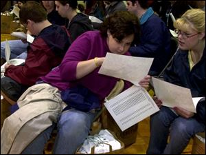 Carrie White, left, and Sarah Hart study their routes during a meeting in Calvary Assembly of God's gym.