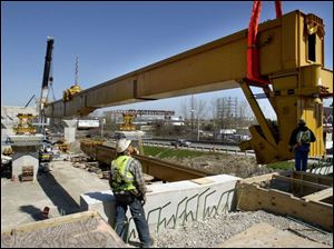 Two cranes, working in tandem, hoist into place one of the southbound `underbridge' beams of the new I-280 bridge.