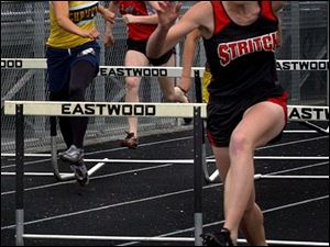 Senior Chelsea Shelnick of Stritch, who repeated as a league champ, leads a hurdle event.
