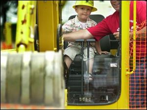 Grant Denhof, 3, whose mother says he's `obsessed' with large machinery, gets a chance to operate one at COSI with the help of Tony Farkasdi of the Ohio Operating Engineers.