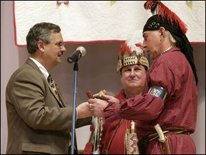 United Methodist Bishop Bruce Ough, left, receives a peace pipe from Larry 'Ayapia' Eveland, a Shawnee Indian from Cincinnati, as the two exchange gifts of reconciliation. Looking on is Rev. Fred Shaw, a Methodist pastor and Shawnee storyteller.