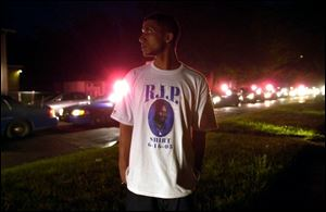 Jomo Brooks, 27, watches police cars parade past with lights and sirens on to signal the start of a cur