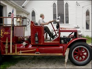Firefighter Bob Hintz pulls the Clyde Fire Department's old-fashioned Clydesdale fire truck, produced in Clyde, out of the city's museum.