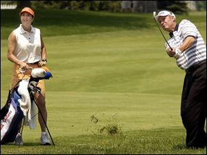 Buddy Alexander, one of 29 amateurs in the field, plays a practice round at Inverness. His wife, Joan, is his caddie.