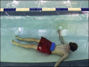 In a training session, a lifeguard lies at the bottom of a pool equipped with the Poseidon system in Medina, Ohio.