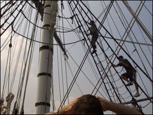 A tourist on the Bounty watches Luke Elliott, top, and Mitchell Bandklayder practice climbing the rigging on their second day of training. The ship was in Fairport, Ohio.
