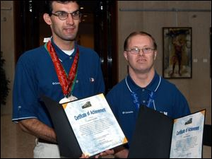 Andy Palmer and James Reiter show the certificates of achievement given them by Lucas County commissioners.