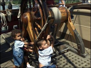 Eshon Howard, 4, behind his brother Julian Howard, 1, and Jaden Fordham, 4, right, take the wheel of the Bounty.