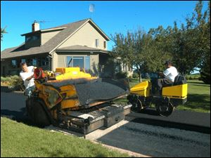 Tony Morlock, of Morlock Asphalt, runs the paving machine and Josh Miller the roller in Grand Rapids, Ohio.