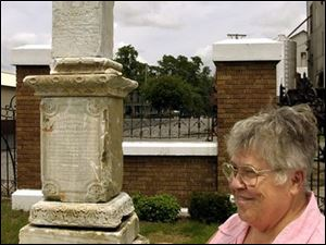 `We just told them there's a surprise,' says Helen Kaverman, a cemetery board member, speaking of the kin of Delphos' founder. Next to her stands the newly discovered 145-year-old monument to the Rev. John Otto Bredeick the family members will see on their visit on Aug. 1.