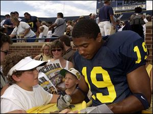 Willis Barringer signs autographs yesterday for Michigan fans on photo day - as a safety, not a cornerback.