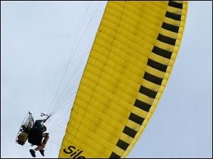 Wally Shilts of New Paris, Ohio, prepares to land at Ohio's annual Motorized Paragliding Gathering in Perrysburg.