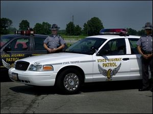Highway Patrol troopers Ryan Stewart and Ron Anderson are beside a new white patrol car.