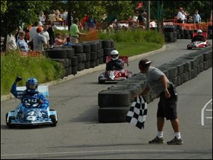 EARLY VICTOR: Giving the checkered flag to Doug Brimmer, driver of Dana car No. 4, is Jason Sanderson, flagman during one of the heats in the 2003 Grand Prix race at Owens Corning World Headquarters Saturday.