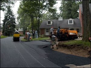 Jennite employees work on a driveway. The Toledo company does paving and sealing.