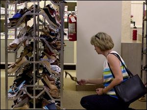 Diane Detterline of Sylvania checked out a shoe sale last week at the Sears store at Toledo's Westgate.
